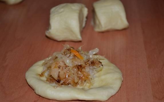 Разделите тесто на небольшие шарики, из каждого раскатайте лепешки и поместите внутрь начинку. Сформируйте пирожки.