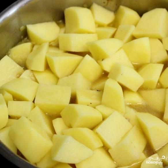 4. Картошку выложите на мясо с морковью. Не перемешивайте! Пусть картофель готовится сверху на пару. Добавьте воду так, чтобы она покрывала картошку до середины. Доведите до кипения, затем снизьте огонь до среднего и тушьте блюдо под крышкой в течение 25-30 минут.