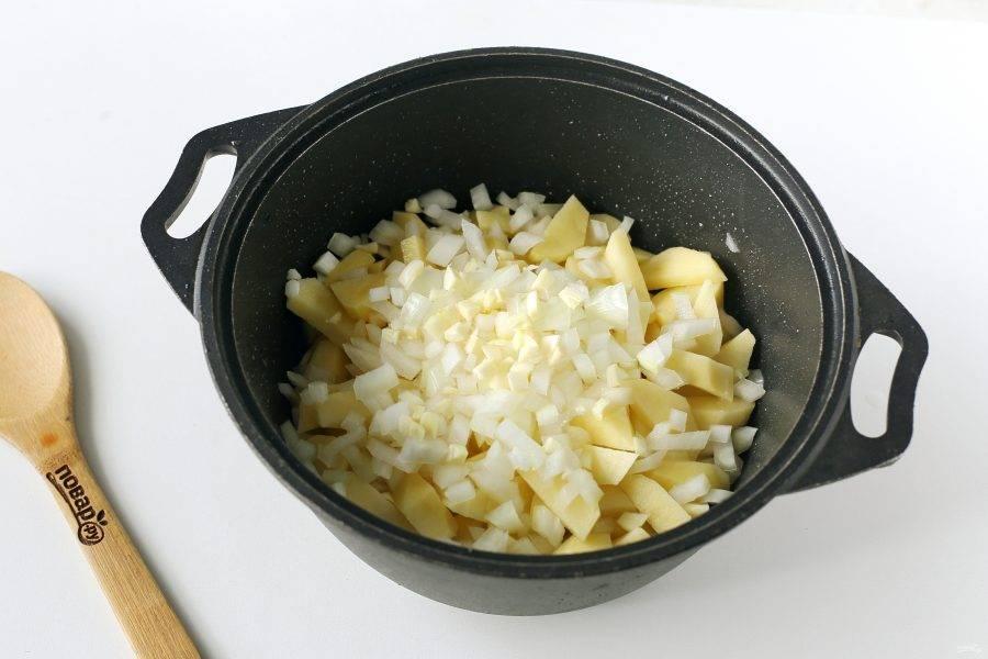 Выложите нарезанный кубиками лук и чеснок. Перемешайте и тушите под крышкой на среднем огне до готовности картофеля.