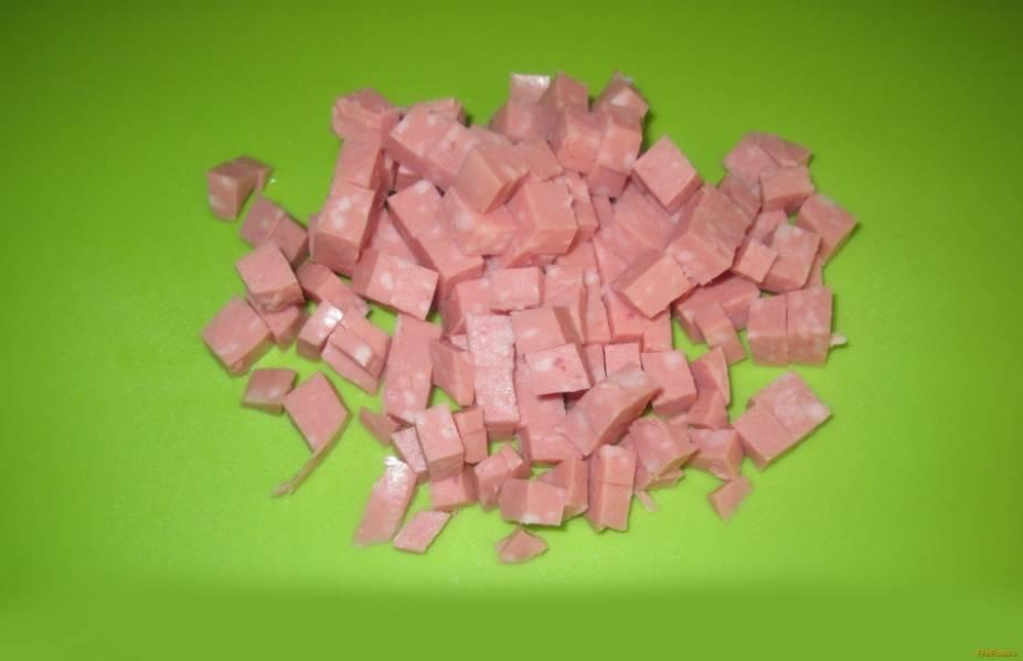 Вареную колбасу нарезаем кубиками.