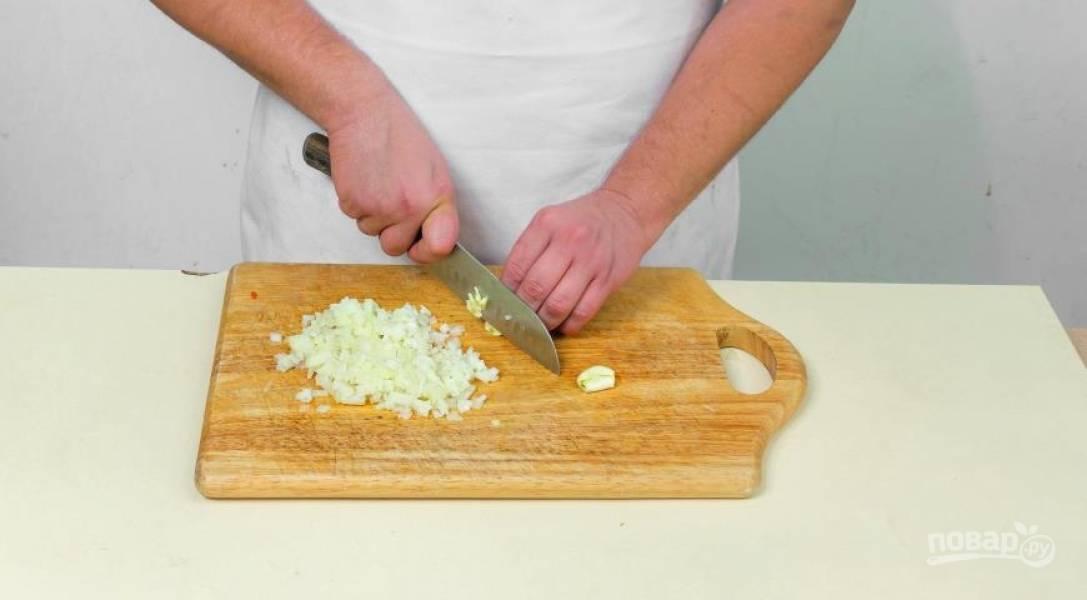 Очистите и мелко нарежьте лук и чеснок. В кастрюле с толстым дном разогрейте немного масла, обжаривайте лук и чеснок в течение 5 минут.