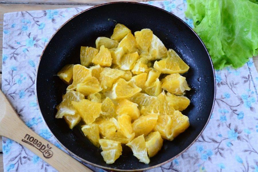 А тем временем приготовьте соус. На сковороде растопите сливочное масло. Апельсин очистите и порежьте на небольшие кусочки. Отправьте апельсин в сковороду и прогрейте его на среднем огне, чтобы он начал выделять сок. Затем добавьте кетчуп, влейте 120-150 мл воды и перемешайте. Готовьте на медленном огне 5-7 минут.