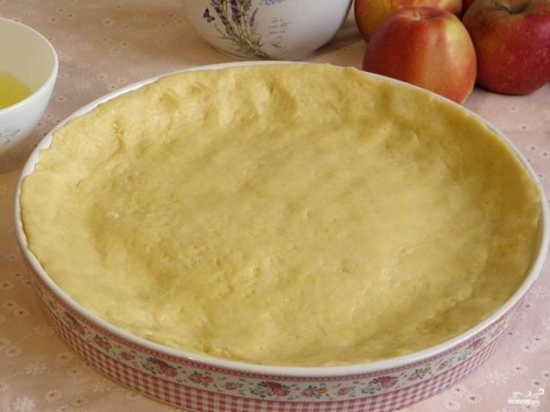 Форму, в которой будете печь пирог, смажьте оливковым маслом. Тесто разровняйте по форме, не забудьте сделать бортики.