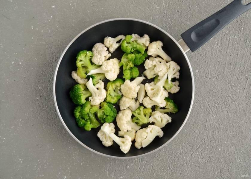 Добавьте брокколи и цветную капусту, потомите их под крышкой 3 минуты.