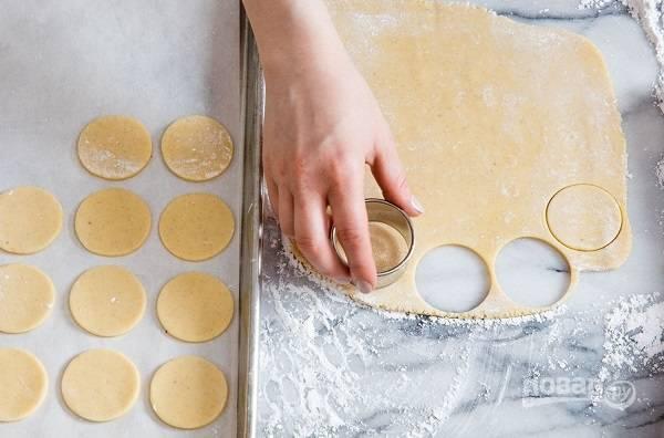 5. Разогрейте духовку до 180 градусов. Раскатайте тесто довольно тонко. Вырежьте около 50 небольших кружочков, которые выложите на противень, застеленный пергаментом.