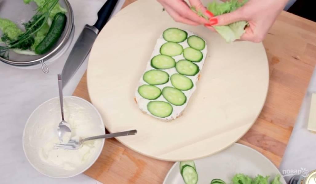 4. Выложите слой нарезанной рыбы и укроп, прикройте вторым слоем хлеба, смазав его заправкой. На второй слой хлеба выложите нарезанные огурцы и листья салата, прикройте третьим слоем хлеба.