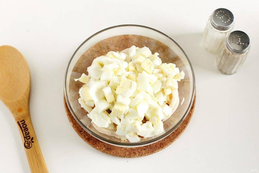 Яйца очистите и нарежьте кубиками. Отправьте к остальным ингредиентам.