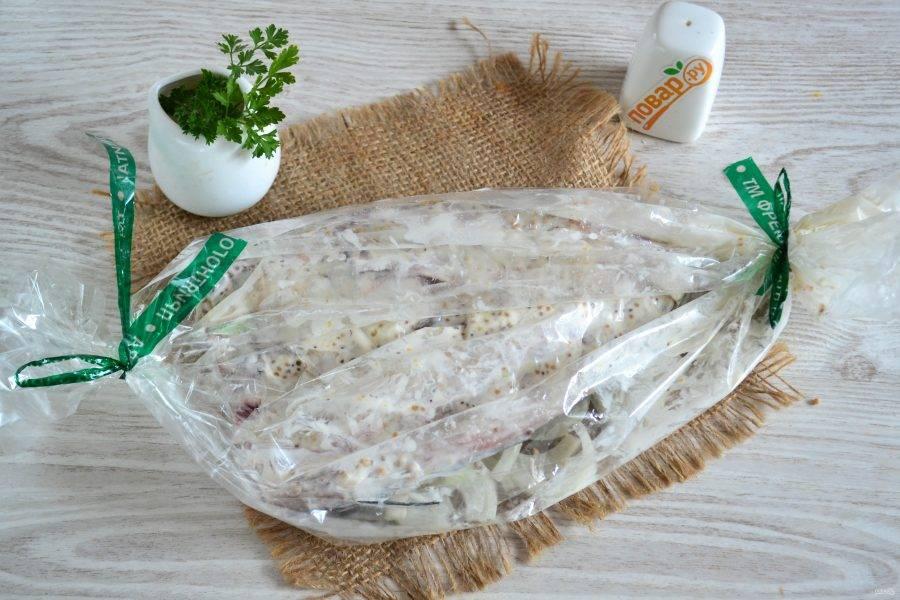 Сверху на лук положите скумбрию. Завяжите рукав с другой стороны. Запекайте скумбрию в духовке при температуре 200 градусов 30-40 минут. Все зависит от духовки. За 10 минут до готовности рукав разрежьте, чтобы рыбка подрумянилась сверху.