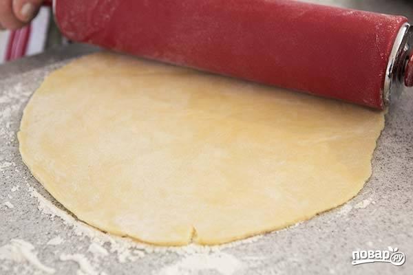 4. Тесто разделите на две части, каждую тоненько раскатайте на присыпанной мукой поверхности. Подготовьте жаропрочную форму, застелите её пергаментом или смажьте маслом. Выложите один пласт теста на дно. Отправьте в разогретую духовку минут на 15 (сверху можно накрыть корж пергаментом и присыпать горохом, чтобы он не поднимался в процессе).