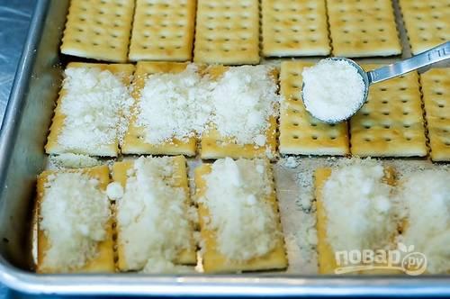 2. Посыпьте каждый крекер тертым сыром.