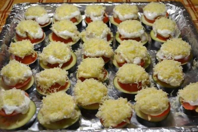 Выкладываем по ложечке сметаны с чесноком, и посыпаем тертым сыром.