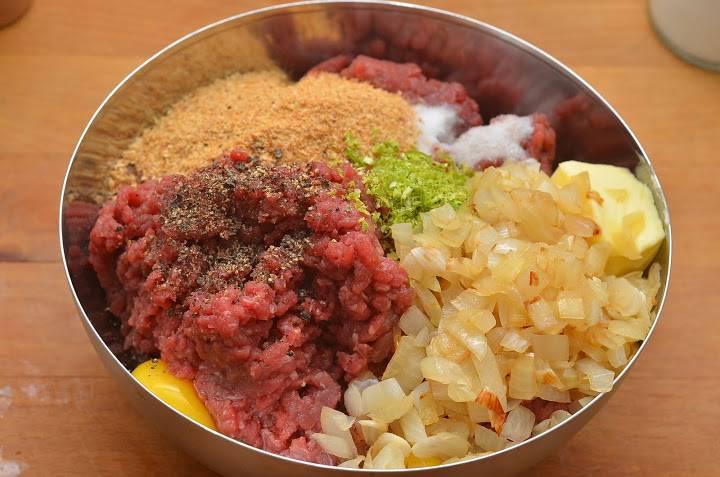 3. Мясо необходимо вымыть, просушить и пропустить через мясорубку. Для этих котлет можно использовать говядину, свинину или сочетание нескольких видов мяса. В фарш добавить яйца, хлеб или сухари, обжаренный и слегка остывший лук. Посолить и поперчить по вкусу. Дополнительный аромат может дать немного цедры лимона или лайма.