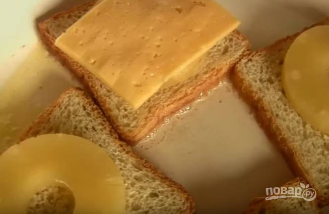 4. Сыр нарежьте тоненькими пластинками. Выложите их поверх ананаса.