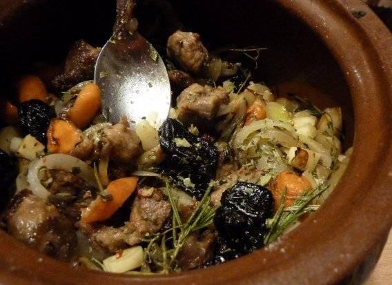 Выкладываем овощи в горшочек на мясо, добавляем ягоды можжевельника и чернослив, перемешиваем верхний слой.