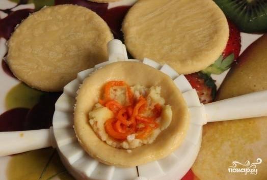 7. Выложите на середину каждой заготовки начинку и морковку по-корейски. Слепите пирожок или воспользуйтесь специальным приспособлением для лепки фигурных вареников. Противень смажьте маслом, выложите на него пирожки. Дайте минут 15-20 постоять. Вилкой взболтайте яичный белок,  смажьте им пирожки сверху.