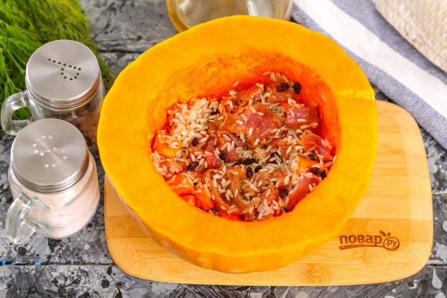 Тыкву очистите от семян, стараясь не повредить или не пробить дно, промойте. Выложите внутрь овоща приготовленную начинку. Очистите репчатый лук от кожуры и нарежьте.