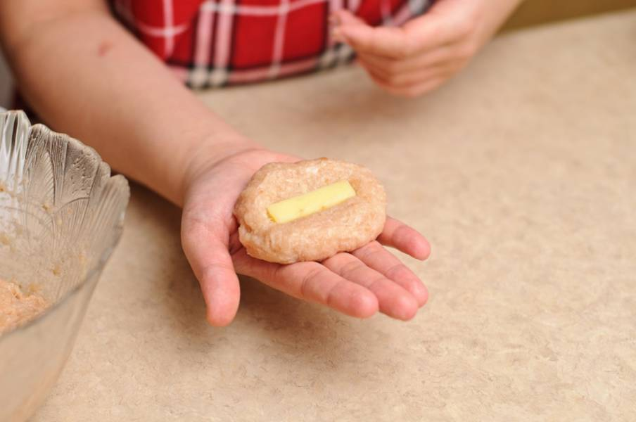 6. Сырок порежьте полосками. Смоченными в воде руками лепим продолговатый блинчик, в центр которого выкладываем приготовленный кусочек сыра.