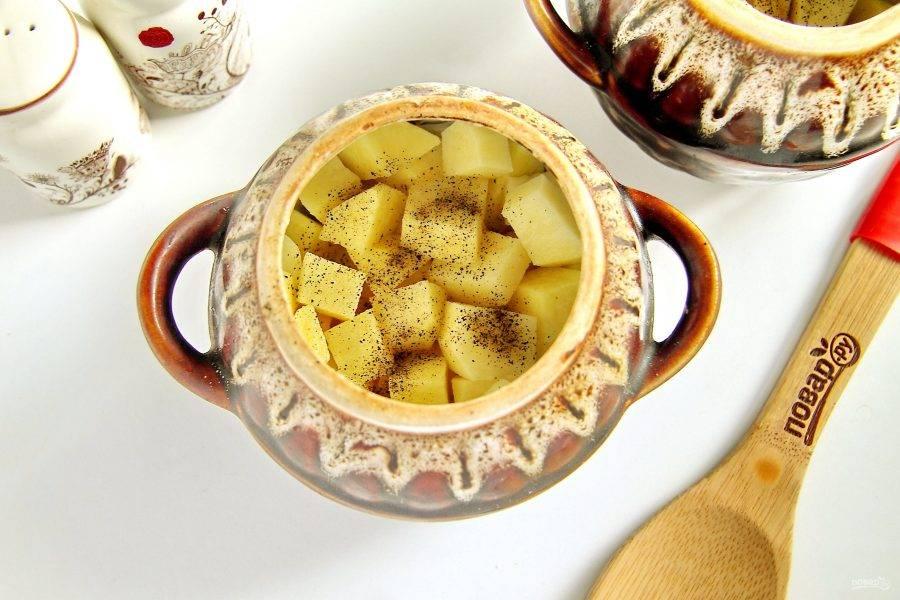 Смажьте горшочки сметаной. Положите на дно картофель, посолите и добавьте перец по вкусу.