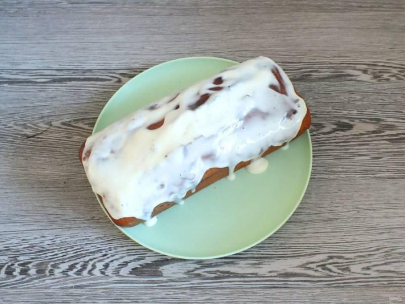 По истечении времени, достаньте готовый пирог из духовки. Извлеките из формы, переложите на блюдо. Еще теплый пирог залейте сладкой сметаной.