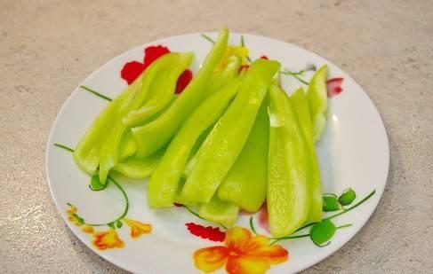 Сладкий перец очищаем от семян и плодоножки, промываем его и нарезаем вдоль на полоски.