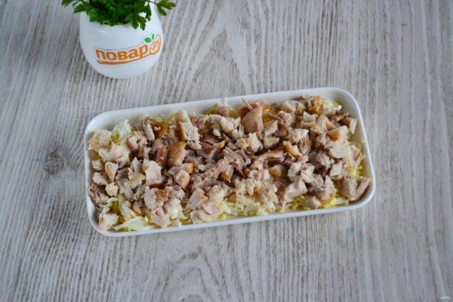 Куриное мясо отделите от кости и мелко нарежьте. Выложите вторым слоем и также совсем чуть-чуть смажьте майонезом.