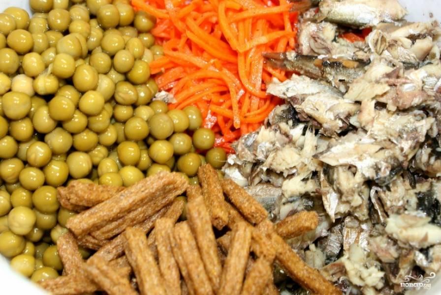 Переложите в глубокую салатницу шпроты и разомните их вилкой. Добавьте корейскую морковь, горошек и сухарики.