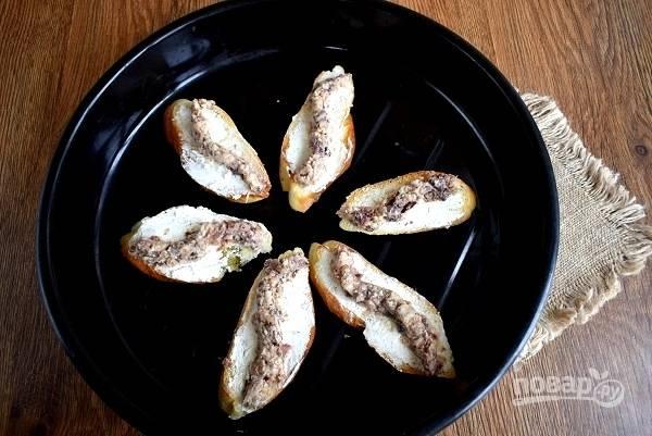 Слейте жидкость с сардин, разомните рыбу вилкой. Сыр намажьте на ломтики багета. Сверху выложите 1-2 столовые ложки измельченных сардин. Запекайте в разогретой до 180С духовке в течение 2-3 минут.