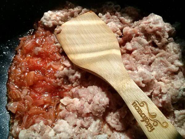 Пока варятся макароны, подготовьте фарш. Мелко нарезанный лук пассеруйте на разогретом оливковом масле. Добавьте мелко порезанную  паприку и томатный сок с мякотью, немного протушите, а затем добавьте фарш. Хорошо перемешайте и тушите 5 минут, затем добавьте сливки. Тушите до испарения жидкости.