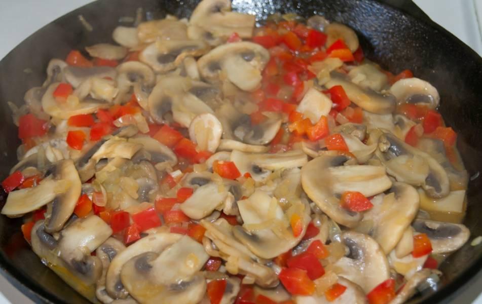 Приготовим соус. Разогреваем в сковороде оливковое масло, выкладываем измельченный репчатый лук, шампиньоны и перец. Обжариваем 5 минут, постоянно помешивая.