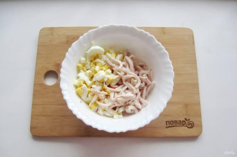 Кальмары очистите от пленок, удалите внутренности. Помойте внутри и снаружи. Отправьте в кипящую воду на 3 минуты и после выложите на тарелку. Охладите, нарежьте тонкой соломкой. Добавьте в салат.