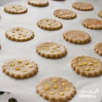 Раскатываем тесто в достаточно тонкий пласт. Вырезаем из пласта печенье (форма - какая вам больше нравится). Если есть желание, печенье можно украсить измельченным миндалем или присыпать сахаром. Выкладываем печенье на противень, застланный пергаментной бумагой.