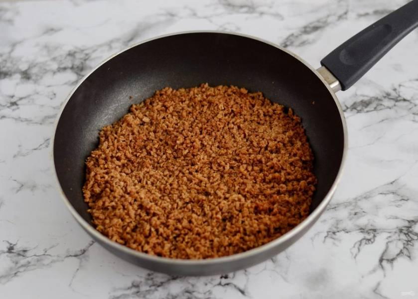 Добавьте соевый соус, томатную пасту, грибную приправу, хорошо перемешайте. Начните постепенно вливать горячую воду и помешивать фарш. Жидкости должно быть столько, чтобы соевые гранулы полностью размягчились, но не больше. Обжарьте фарш ещё 3-4 минуты.