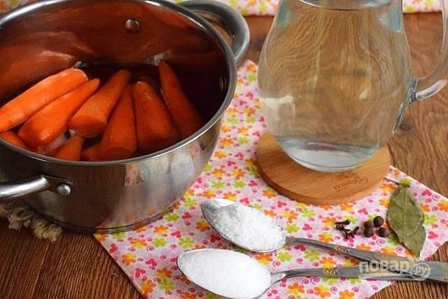 Морковь и специи поместите в кастрюлю с толстым (или двойным) дном, залейте водой, накройте крышкой. Доведите до кипения, бланшируйте в течение 10 минут, слейте воду. Приготовьте рассол: в кипятке размешайте соль и сахар.