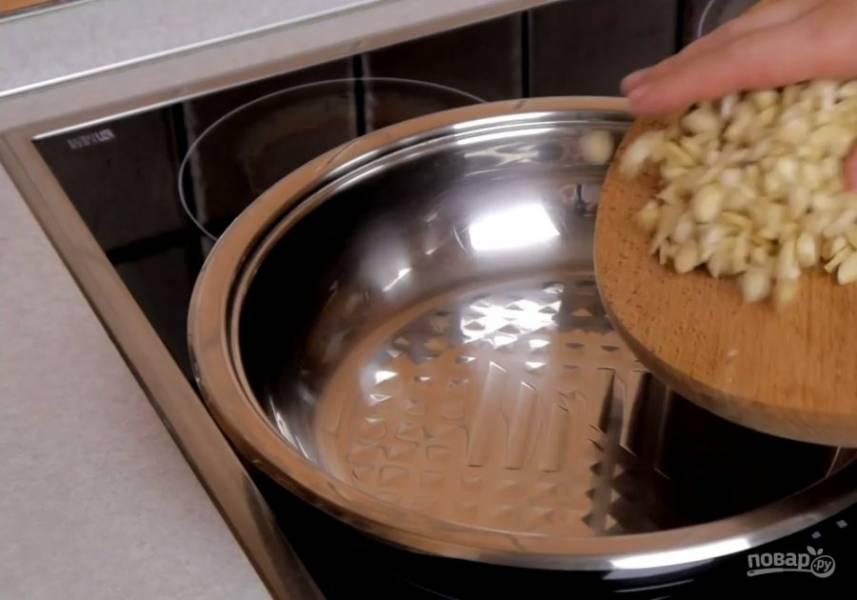 1. Миндаль залейте кипятком и оставьте на 10 минут. Очистите от кожицы, порубите и обжарьте до золотистого цвета. Остудите. Сахар соедините с водой и проварите, не размешивая, до золотистого цвета. Добавьте орехи и перемешайте.