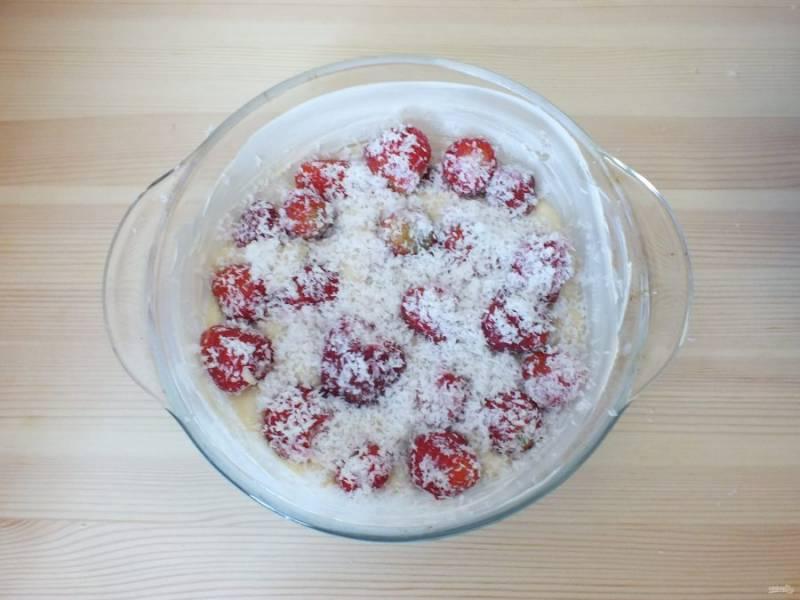 Сверху залейте 1/2 частью теста, выложите опять клубнику, присыпьте кокосовой стружкой.
