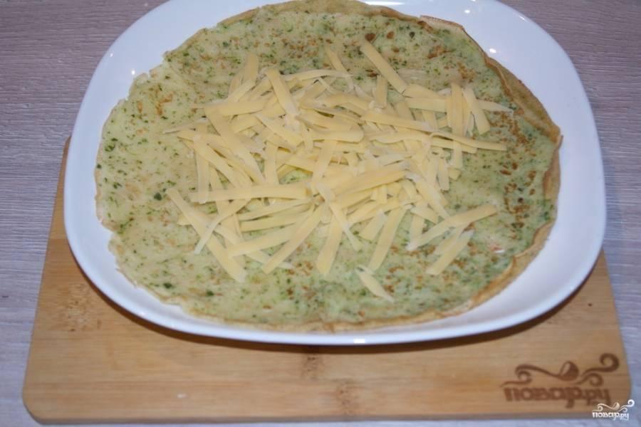7. Натрите на крупной терке твердый сыр. На каждый блинчик выложите сыр.