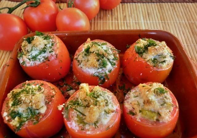 3. Начинив все плоды посыпаем сверху тертым сыром и отправляем в горячую духовку. Запекаем фаршированные помидоры рыбой в домашних условиях около 30 минут, после чего подаем в горячем виде.