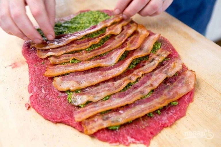 2.Нарежьте бекон ломтиками и обжарьте его до полуготовности. Выложите отбитое мясо, смажьте его слоем пасты из петрушки (песто), выложите ломтики бекона поперек волокон.