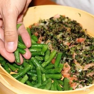 Выкладываем в пароварку нашу рыбу и стручковую фасоль. Сверху слегка поливаем маслом и солим.