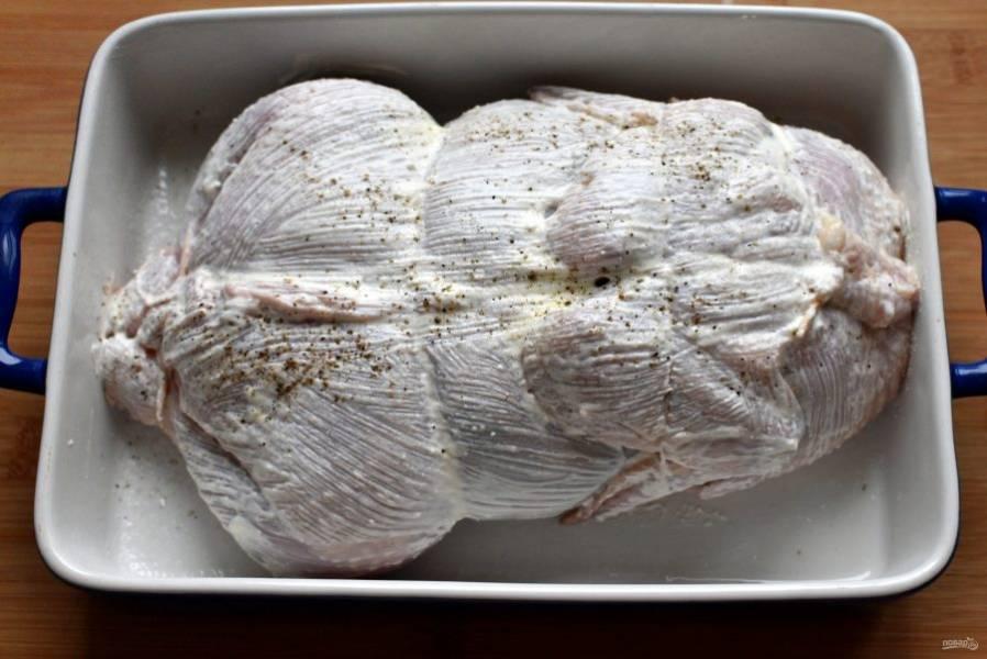 Уложите курицу в форму для запекания спинкой вверх, смажьте половиной сметаны, поперчите сверху. Отправьте в разогретую духовку и запекайте при 180 градусах минут 10, пока корочка чуть не схватится. Затем осторожно переверните курицу грудкой вверх, смажьте остатками сметаны и запекайте еще около часа, периодически поливая курицу выделяющимся соком.
