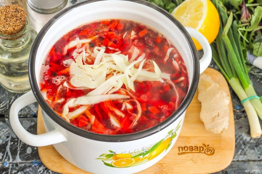 """Нарежьте белокочанную капусту, добавьте в кастрюлю. Сразу же влейте лимонный сок, иначе капуста """"вытянет"""" цвет борща."""