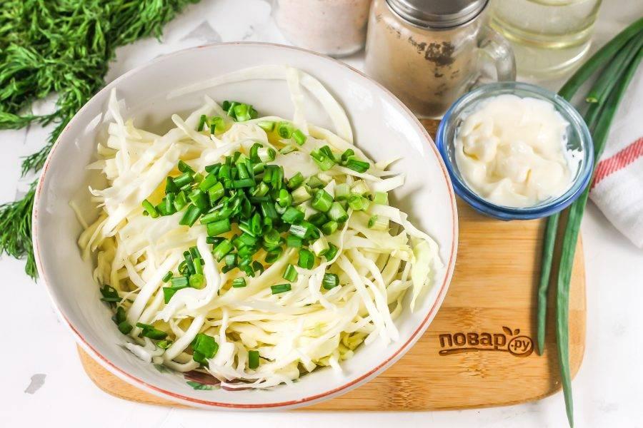 Капусту тонко нарежьте, выложите нарезку в глубокую емкость. Промойте и измельчите зеленый лук. Добавьте к капусте вместе с щепоткой соли. Тщательно помните всю нарезку, чтобы она выпустила сок.