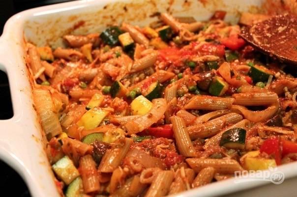 4. Добавьте макароны, горошек на противень и соус. Аккуратно перемешайте.