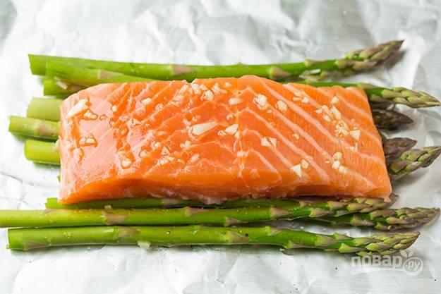 3.Очистите чеснок и нарежьте его мелко. Выложите поверх спаржи кусочек рыбы, полейте его несколькими каплями оливкового масла, добавьте измельченный чеснок.