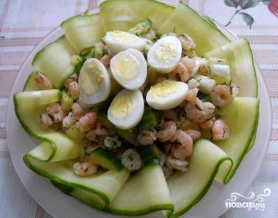 Украшаю тарелку полосками из огурца, выкладываю салат и сверху добавляю половинки яиц.
