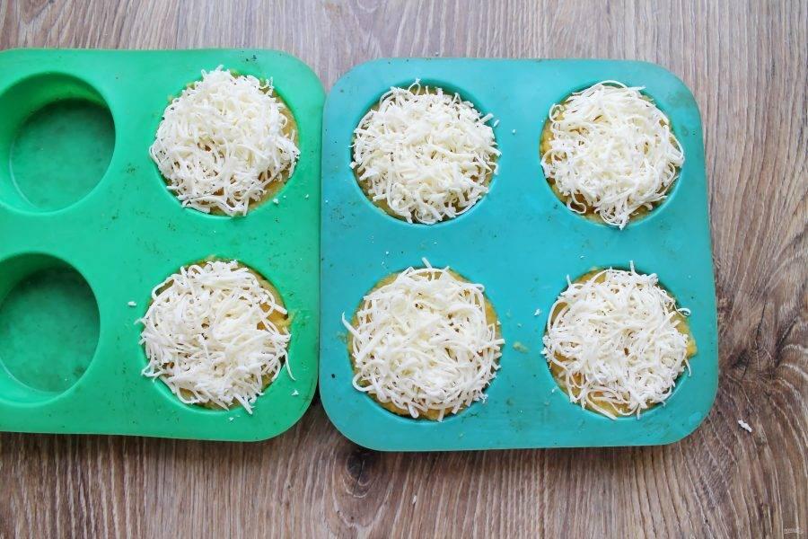 Натрите сыр на средней терке и засыпьте верх кексов.