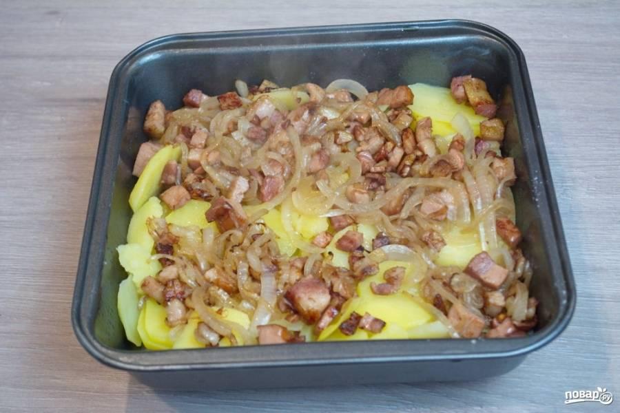 На картофель выложите обжаренные бекон с луком. Распределите равномерно.