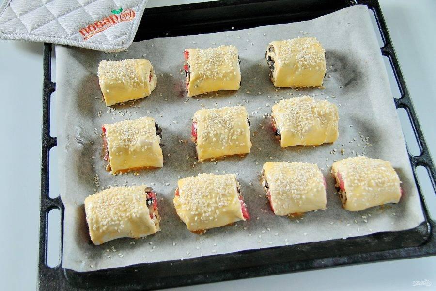 Сверните плотный рулет и разрежьте на 4-6 частей. Выложите заготовки на противень, застеленный пергаментом, смажьте желтком и посыпьте кунжутом. Выпекайте при 200 градусах около 30 минут.