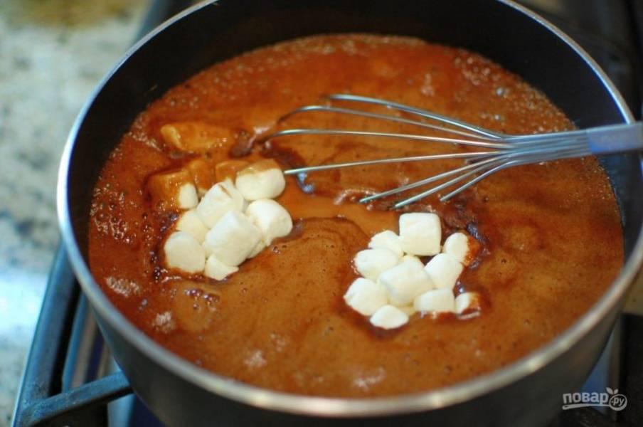 2.В сотейник выложите 120 грамм сливочного масла, растительное масло, 3 столовые ложки какао, 1 стакан колы. Отправьте сотейник на огонь и после закипания добавьте маршмеллоу, сразу уберите с огня.