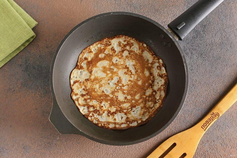 Разогрейте сковороду и смажьте ее маслом. Налейте половину стандартного половника теста и распределите его равномерно по всей поверхности. Жарьте блинчики с двух сторон до готовности.